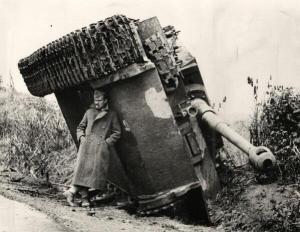 Un soldato britannico nascondersi dalla pioggia sotto un carro armato rovesciato. Italia, 1944
