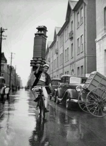 Un ragazzo consegna per un ristorante di Tokyo portando un vassoio di Soba Bocce