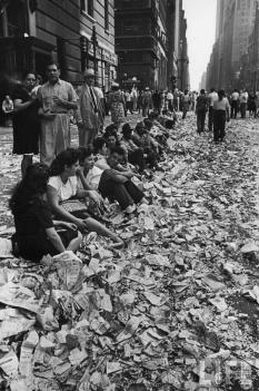 La gente si siede sul marciapiede tra i coriandoli del corteo che celebra la fine della seconda guerra mondiale. 14 ago 1945