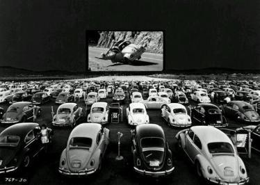Volkswagen Beetle guardano 'Herbie - The Love Bug' in un teatro drive-in, c. 1960