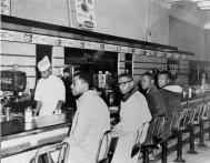 4 studenti siedono in posti designati per i bianchi. Greensboro NC, 1960