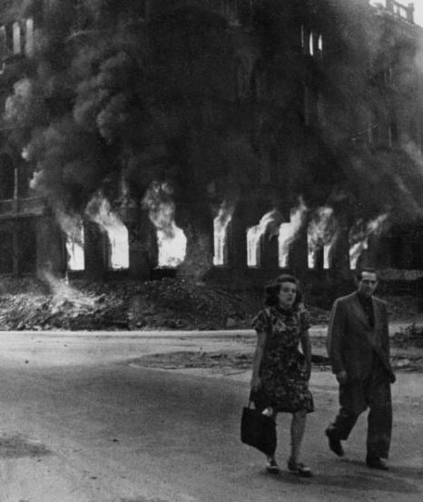 Una coppia cammina per le strade di Berlino in fiamme negli ultimi giorni della guerra, 1945