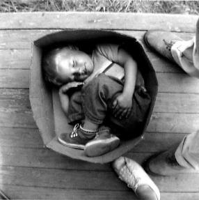 Un bambino senzatetto dorme in una scatola a Seattle - Hooverville, 1933