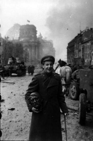 Un soldato russo con la testa della statua di Adolf Hitler. Berlino, circa maggio 1945