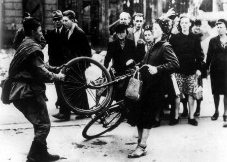 Un soldato russo cerca di rubare la bicicletta a una donna, ma lei si rifiuta. Berlino, 1945