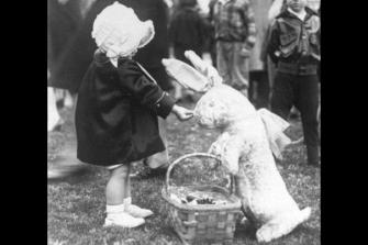 Una bambina dà caramelle a un coniglietto pasquale 1929