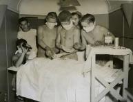 Un giovane chirurgo e i suoi assistenti eseguono un intervento chirurgico d'urgenza su un soldato ferito. 1944