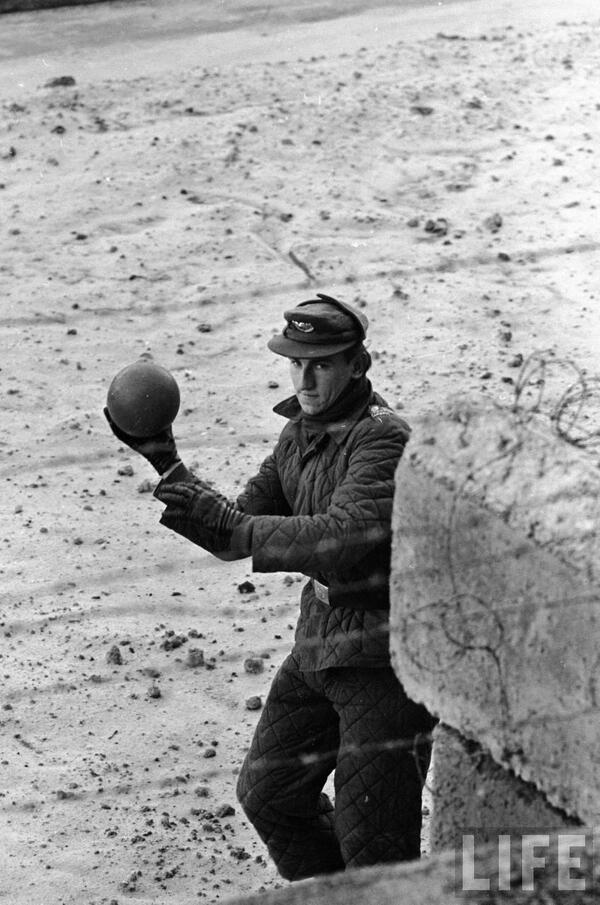 Una guardia della Germania dell'Est lancia una palla sopra il muro di Berlino. Foto di i Paul Schutzer, 1962