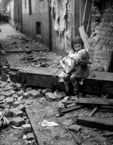 Una bambina inglese conforta la sua bambola tra le macerie della sua casa colpita dalle bombe nel 1940
