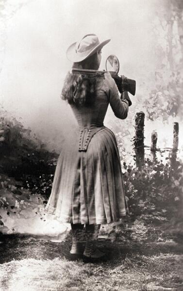 Annie Oakley spara sopra la sua spalla con uno specchio in mano