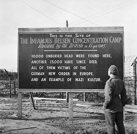Militare britannico legge un cartello al campo di concentramento di Bergen-Belsen, maggio 1945