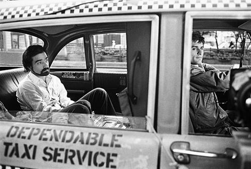 Martin Scorsese seduto dietro nel taxi di Robert De Niro sul set di Taxi driver (1975)