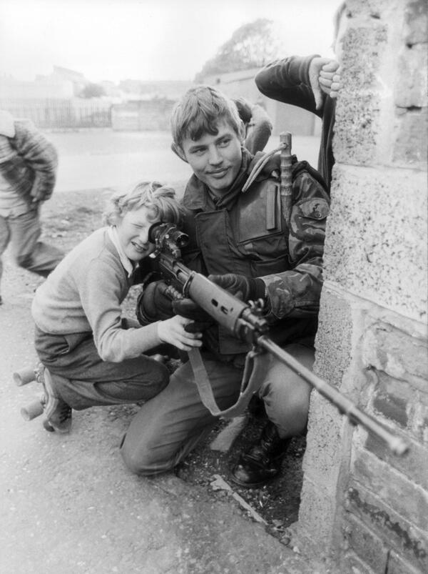 Un soldato britannico lascia che giovane ragazzo guardi attraverso il mirino del suo fucile a Belfast, 1981