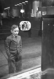 Ragazzo guarda per la prima volta una TV in una finestra negozio di elettrodomestici, 1948