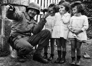 Tre bambine scrutano attraverso il binocolo di un soldato americano dopo la liberazione della Normandia 1944