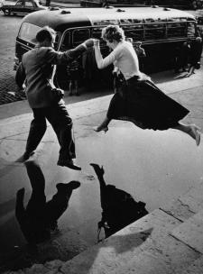 Un uomo dà una donna una mano mentre vola su una grande pozzanghera sul marciapiede, 1960