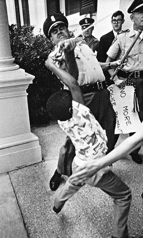 Un poliziotto strappa la bandiera americana a un bambino di 5 anni, Anthony Quinn, Jackson, Mississippi, 1965 (fotografia di Matt Heron)