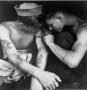 Un marinaio americano tatuato da un compagno di bordo sulla USS New Jersey nel loro cammino verso il Pacifico, dicembre 1944