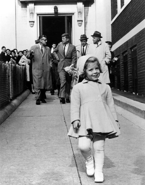 Caroline Kennedy cammina avanti mentre suo padre, JFK, porta la sua bambola. 1 gennaio 1963