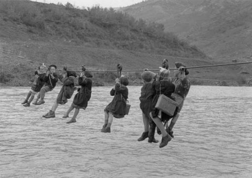 Bambini attraversano il fiume con pulegge per arrivare a scuola nella periferia di Modena, Italia, 1959