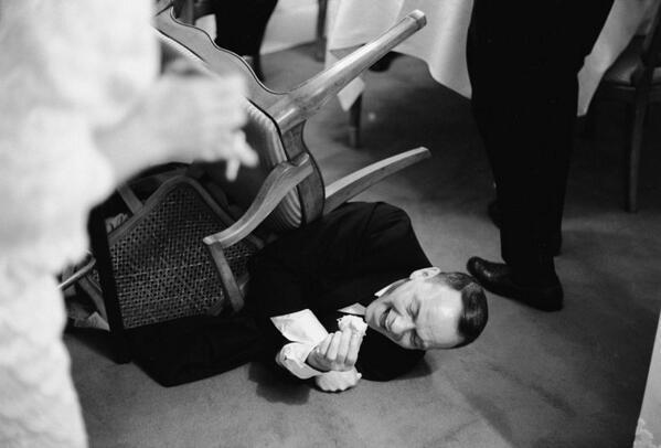 Frank Sinatra cade dalla sedia ridendo per uno scherzo raccontato da Joe E. Brown