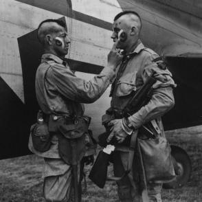 """Soldati americani del """"Filthy Tredici"""" si applicano vernice in viso prima di sbarcare in Normandia 1944"""