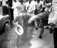Agitatori bianchi danno calci a un uomo nero in Arkansas durante le proteste di desgregazione razziale nel settembre 1957