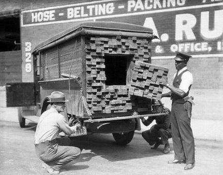 Un agente federale ispeziona un camion di legname dopo aver sentito odore di alcol durante il periodo di divieto, Los Angeles, 1926