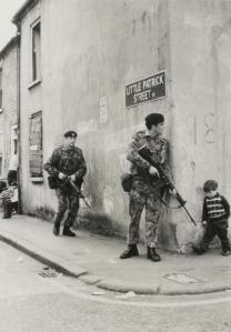 Un ragazzino che cammina con i suoi amici incontra soldati britannici dietro l'angolo a Belfast, Irlanda del Nord. 1973