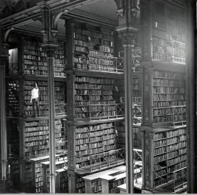 Un uomo cerca fra i libri nella vecchia biblioteca di Cincinnati. La biblioteca è stata demolita nel 1955