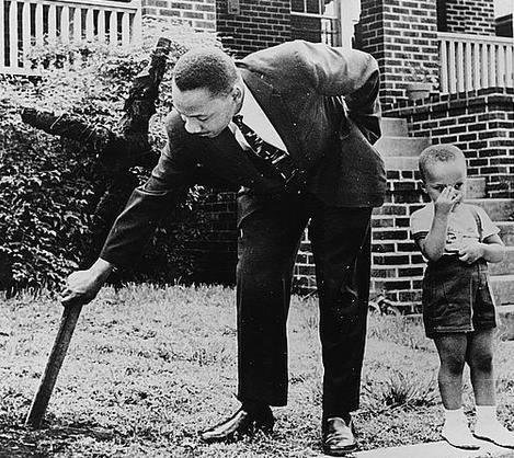 Martin Luther King Jr. rimuove una croce bruciata dal suo cortile con il figlio al suo fianco, 1960