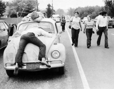 Due frequentatori di Woodstock svenuti sulla loro Volkswagen Beetle, 1969