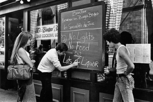 Il proprietario di un ristorante mette un cartello durante il blackout di New York del 13 Luglio 1977