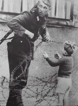 Un soldato tedesco dell'est che aiuta un bambino ad attraversare il Muro di Berlino appena costruito,1961