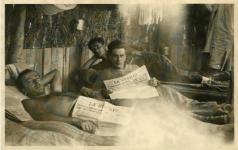 Italiani in Somalia in branda con quotidiano. 1936
