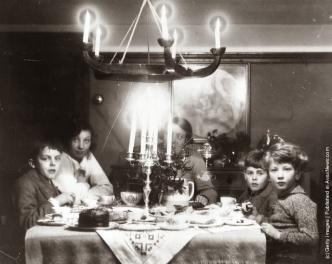 Una famiglia a Natale all'ora del tè con torta al cioccolato, un candelabro e agrifoglio sul tavolo. (Photo by Agenzia fotografica Generale: Getty Images). circa 1935