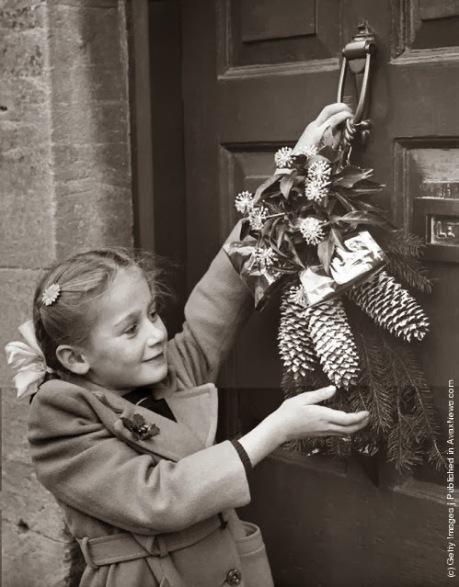 Una bambina appende una ghirlanda di Natale alla porta della sua casa a Northleach, Gloucestershire, in conformità con un vecchio costume locale. (Photo by Fox Foto: Getty Images). 24 dic 1954