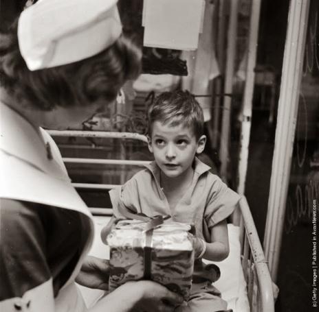 Un giovane paziente del reparto pediatrico del Lenox Hill Hospital, in America, riceve un inaspettato regalo di Natale dall'infermiera Linda Gross. (Photo by Vecchio: Three Lions: Getty Images). circa 1955