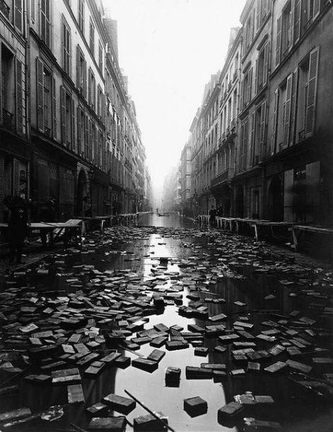 I libri galleggianti della biblioteca lungo una strada durante il Diluvio Universale di Parigi 1910