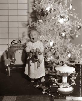 LeRoy, il bambino di un anno stella della Paramount gioca con i suoi nuovi giocattoli sotto l'albero di Natale. (Photo by Hulton Archive: Getty Images). 1933