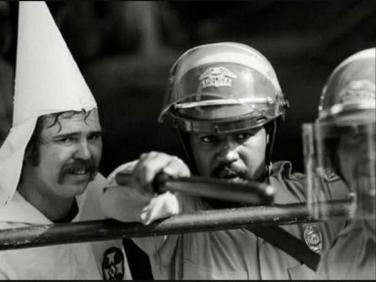 Un poliziotto nero protegge un membro del KKK, mentre i manifestanti stanno chiudendo su di loro in una manifestazione ad Austin, Texas, 1983