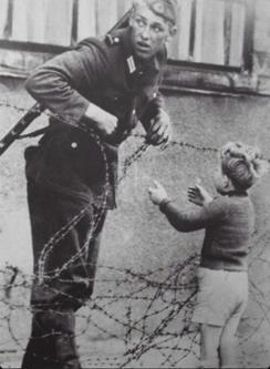Un soldato tedesco dell'est aiuta un bambino a scavalcare il neonato Muro di Berlino, 1961