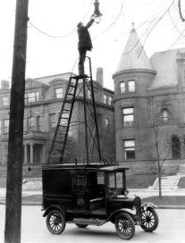 Un uomo cambia una lampada di strada in USA circa 1910
