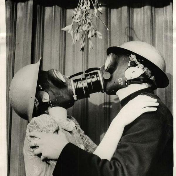 Coppia con maschera a gas si bacia sotto il vischio. Inghilterra 1940