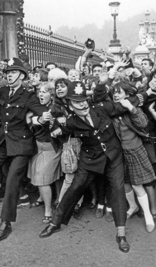La polizia che lotta per frenare i fan dei Beatles fuori da Buckingham Palace nell'ottobre del 1965