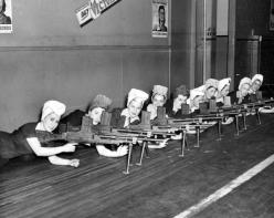 Donne che lavorano nelle fabbriche testano le pistole che hanno prodotto per la seconda guerra mondiale