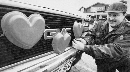 Un tizio adorna la macchina con cuori rossi per San Valentino