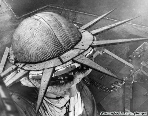 Un gruppo di persone che si sporgono dalla testa della Statua della Libertà a New York, 1930