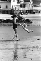 Una madre gioca con il suo bambino sulla spiaggia. [C. 1950]