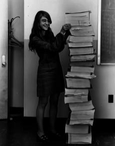 Margaret Hamilton, ingegnere del software principale del Progetto Apollo, si trova accanto al codice che ha scritto a mano e che è stato utilizzato per portare l'umanità sulla luna. [1969]